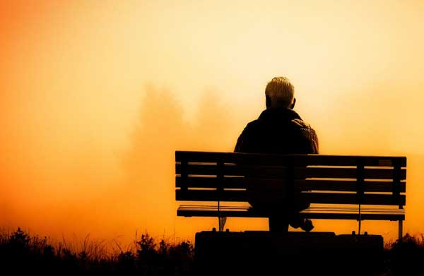 silhouette of man on park bench