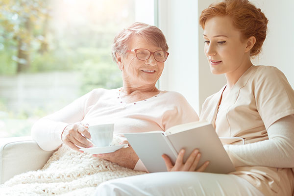 young nurse reading to older woman